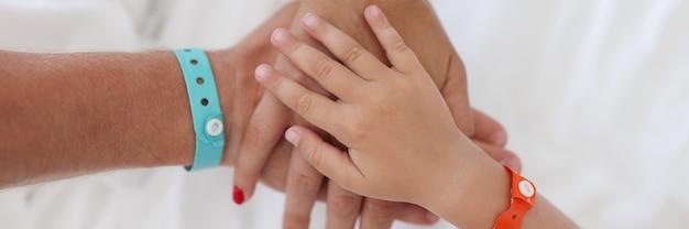 Hände von eltern und kind mit armband werden zusammengefügt