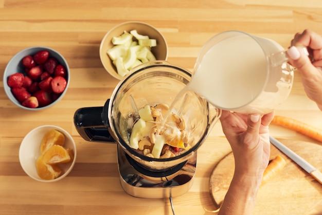 Hände von frauen, die milch mit gehackten zutaten in einen mixer gießen
