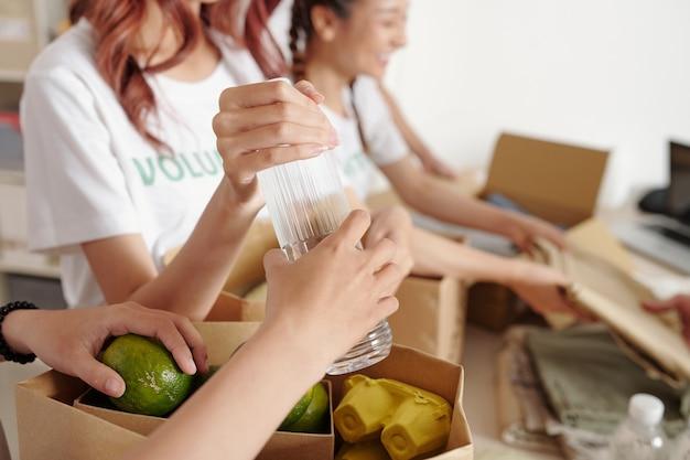 Hände von freiwilligen des wohltätigkeitszentrums, die lebensmittel, wasser und frisches obst in kartons packen
