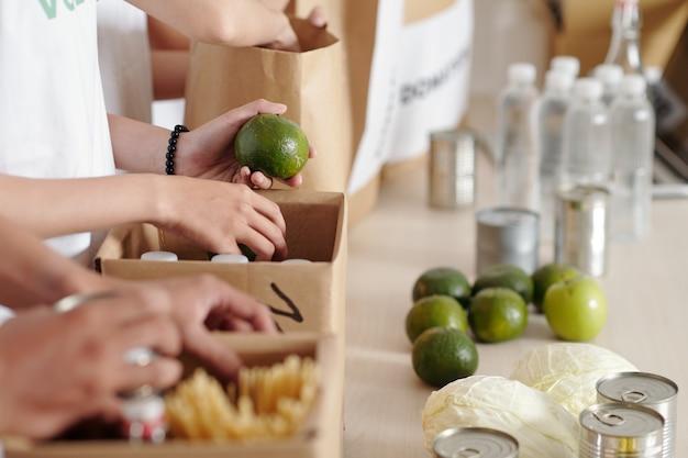 Hände von freiwilligen, die frische lebensmittel in kisten für flüchtlinge oder bedürftige packen