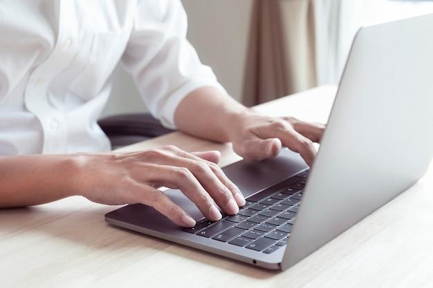 Hände von geschäftsleuten, die im büro arbeiten mann, der tastatur auf laptop tippt