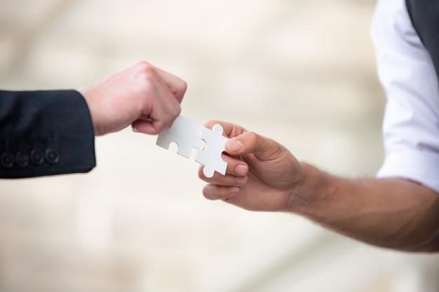 Hände von geschäftsleuten halten papierpuzzle zusammen, zusammenarbeitendes puzzle des geschäftsteams