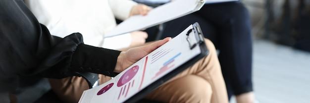 Hände von geschäftsmitarbeitern mit dokumenten und diagrammen mit finanzindikatoren, die auf stühlen sitzen