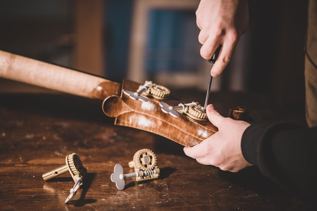 Hände von gitarrenbauern schrauben und bauen einen kontrabass