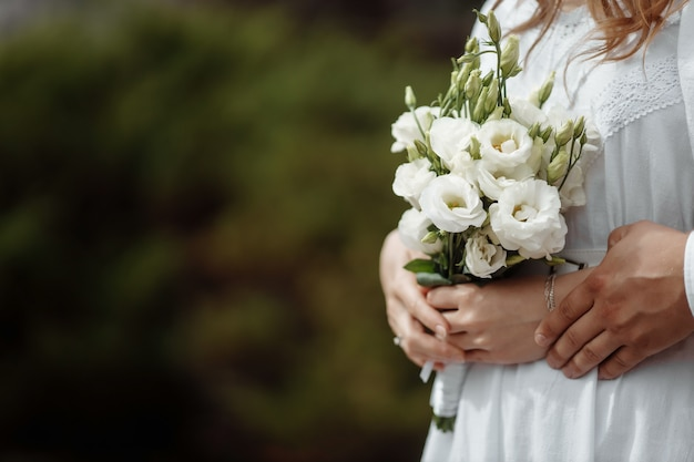 Hände von jungvermählten mit eheringen und einem hochzeitsstrauß jungvermählten
