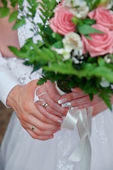 Hände von jungvermählten mit eheringen