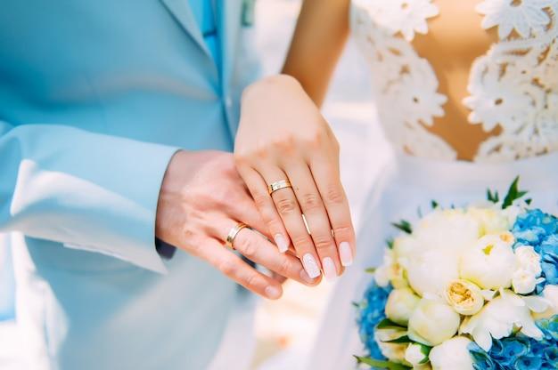 Hände von jungvermählten mit schönen goldenen ringen, nahaufnahme. weißes brautjungfernkleid, blumenstrauß, stilvolle maniküre. perfekte hochzeitszeremonie.