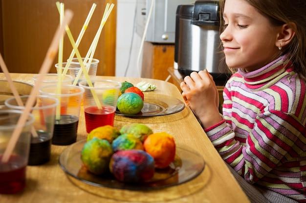 Hände von kindern, die farbstoff verwenden und auf weiß gekochten eiern malen