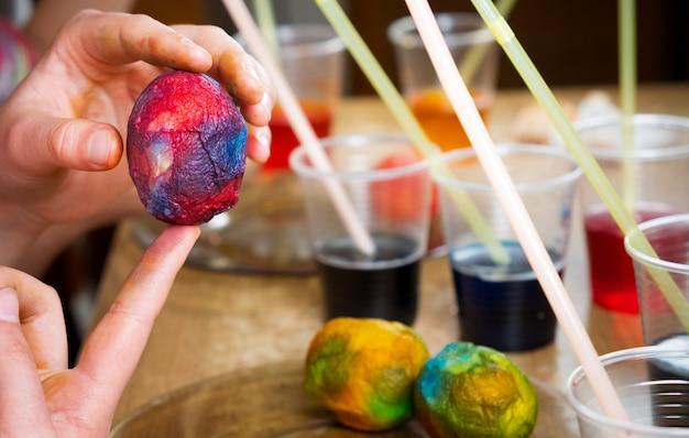 Hände von kindern, die farbstoff verwenden und auf weiße gekochte eier malen, während sie sich auf ostern vorbereiten