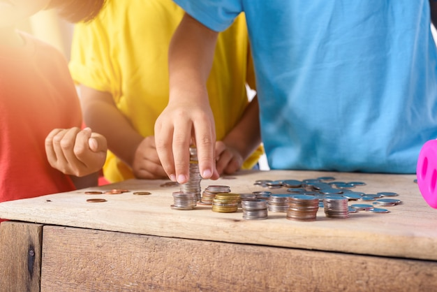 Hände von kindern helfen, münzen in das sparschwein zu setzen, das auf weißen hintergrund lokalisiert wird
