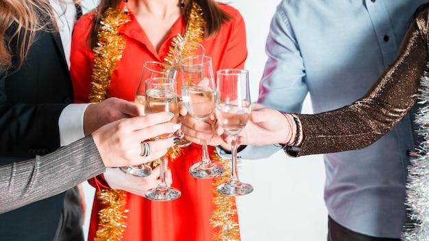 Hände von leuten, die mit champagnerflöten rösten