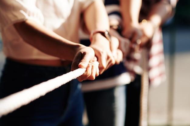 Hände von leuten, die tauziehen, teamwork und wettbewerbskonzept spielen