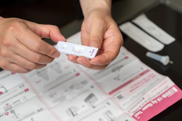Hände von männern, die covid-19-heimantigen-kits verwenden, um auf coronavirus zu testen.