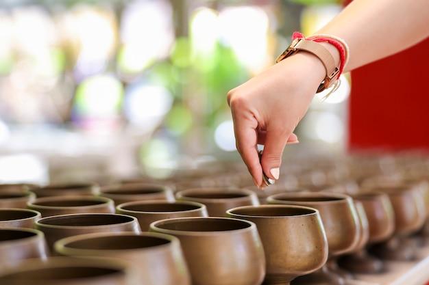Hände von menschen verdienen in der schüssel mit münzen nach dem glauben der lokalen traditionen