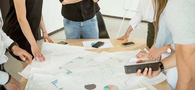 Hände von mitarbeitern über einem tisch mit diagrammen von spielen für das projekt unscharfes bild der hände