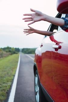 Hände von reisenden durch ein autofenster, das den wind genießt