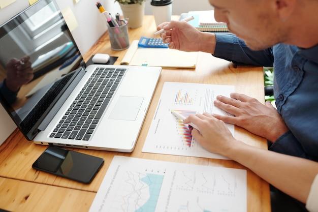 Hände von unternehmern, die sich im büro treffen, um das aufsteigende diagramm im verkaufsdatenbericht zu diskutieren