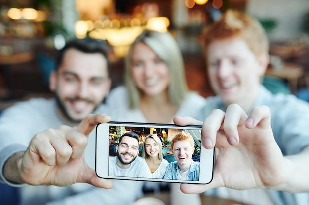 Hände von zwei glücklichen kerlen, die smartphone halten, während foto von ihnen und hübschem mädchen auf touchscreen zeigen