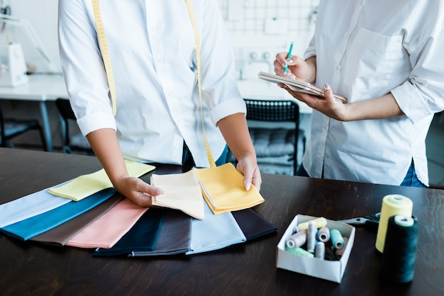 Hände von zwei jungen frauen, die textilmuster für neue modekollektion auswählen und notizen durch tabelle in der werkstatt machen