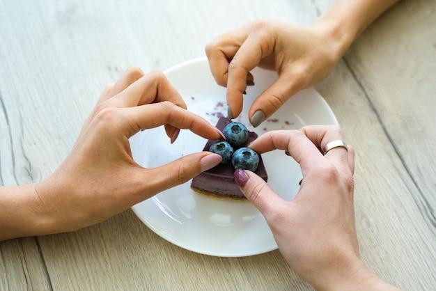 Hände von zwei mädchen, die blaubeeren von der spitze des leckeren käsekuchens auf teller nehmen, während sie einen kuchen zusammen im café essen