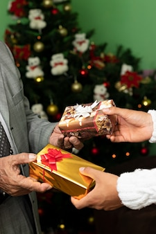 Hände von zwei männern, die sich zu weihnachten kleine geschenke machen