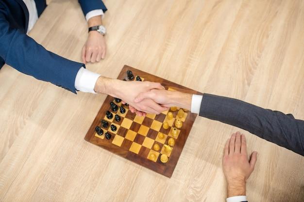 Hände von zwei männern in anzügen, die hände über schachbrett mit figuren vor spiel schütteln
