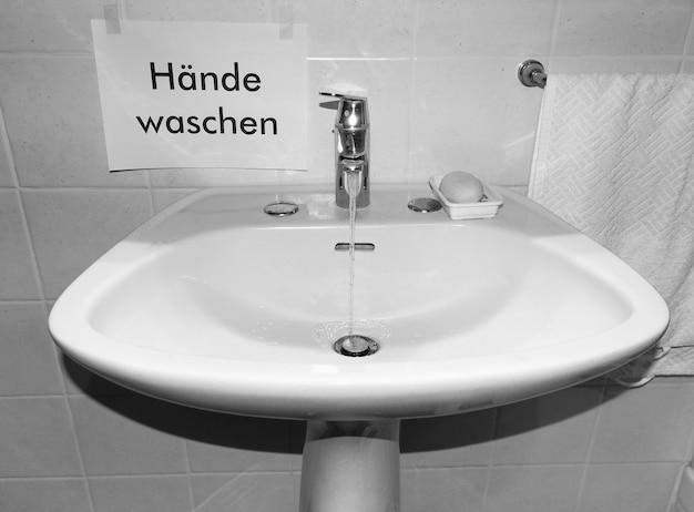 Hände waschen (übersetzung: hände waschen) schild neben waschbecken