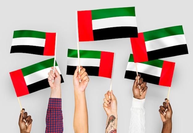 Hände wehende fahnen der vereinigten arabischen emirate