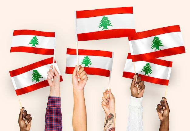 Hände wehende fahnen des libanon