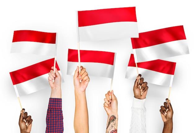 Hände wehende fahnen von indonesien