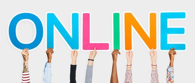 Hände, welche die bunten buchstaben bilden das wort online halten