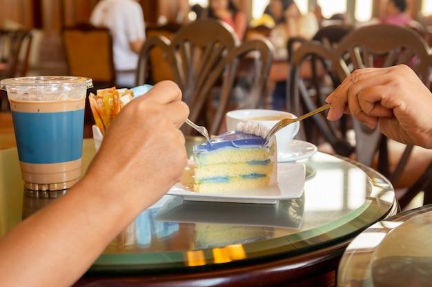 Hände, welche die gabel auf dem tisch isst scheibe der kokosnuss mit kaffee halten.