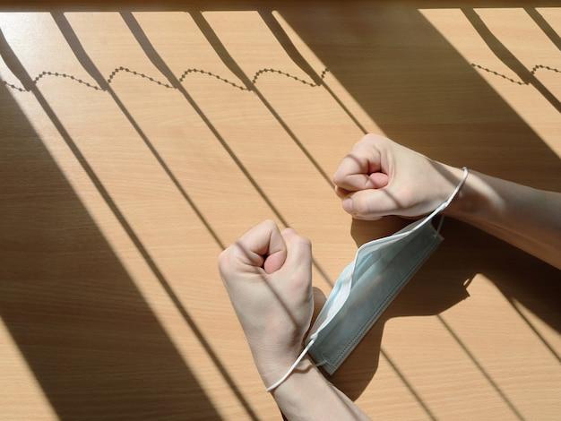 Hände werden zu fäusten geballt und mit medizinischer maske gegen schatten in form eines gitters gefesselt