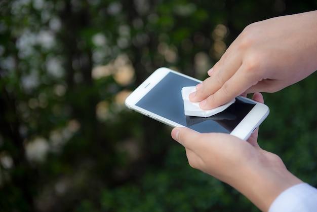 Hände wischen smartphone-bildschirm mit desinfektionstuch