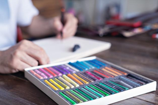 Hände zeichnen mit einer pastellkreide kreide auf papier
