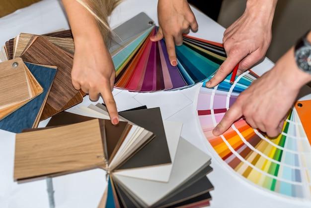 Hände zeigen auf farbmuster zur renovierung