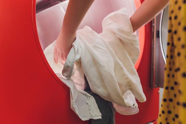 Hände zum laden der wäsche in die waschmaschine der reinigung.