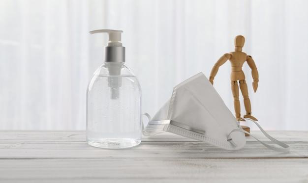 Händedesinfektionsmittel, chirurgische maske, holzpuppe auf holztisch mit weichem weißem hintergrund, während covid-19-quarantäne nach hause.