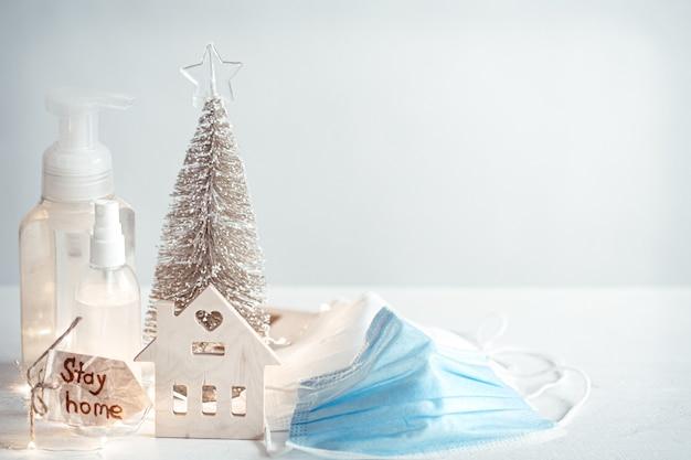 Händedesinfektionsmittel, einweg-gesichtsmasken, details der weihnachtsdekoration auf verschwommener lichtwand. weihnachts- und coronavirus-pandemiekonzept. covid-19.