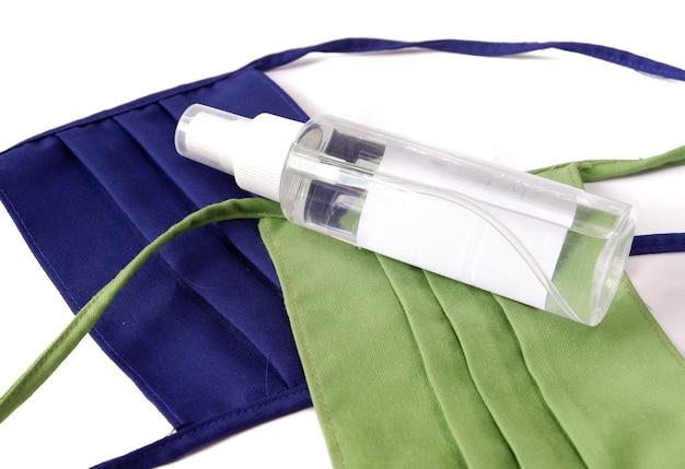 Händedesinfektionsmittel mit maske auf weißem hintergrund