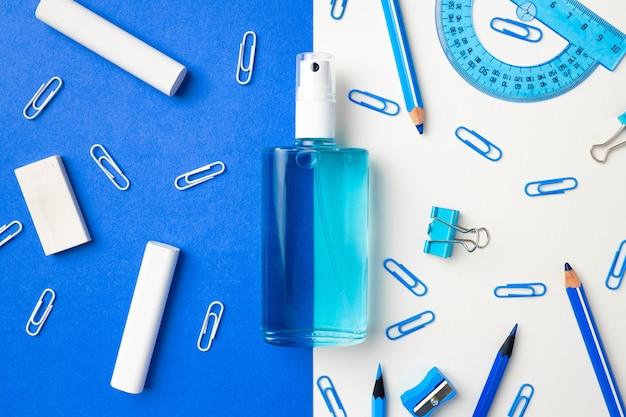 Händedesinfektionsmittel und schulmaterial wie kreide, büroklammern auf blauem und weißem papier, flachgelegt