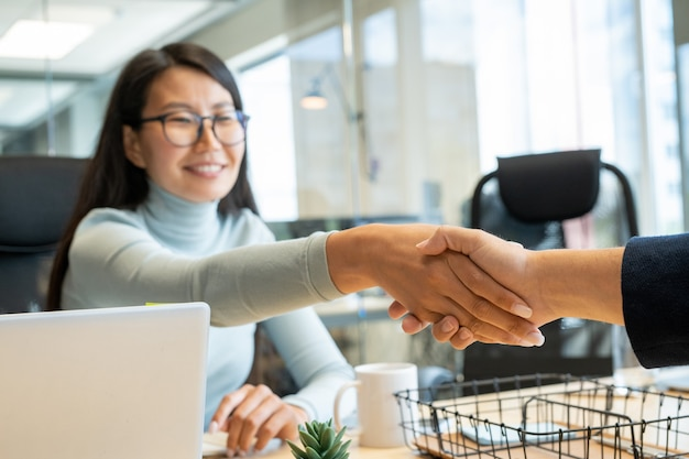 Händedruck der jungen glücklichen geschäftsfrau mit den dunklen langen haaren und ihrem neuen kollegen oder geschäftspartner über dem arbeitsplatz nach dem unterzeichnen des papiers