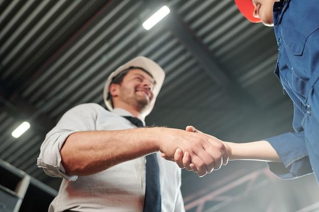 Händedruck des eleganten vorarbeiters und seiner neuen jungen untergebenen zu beginn des arbeitstages in der werkstatt