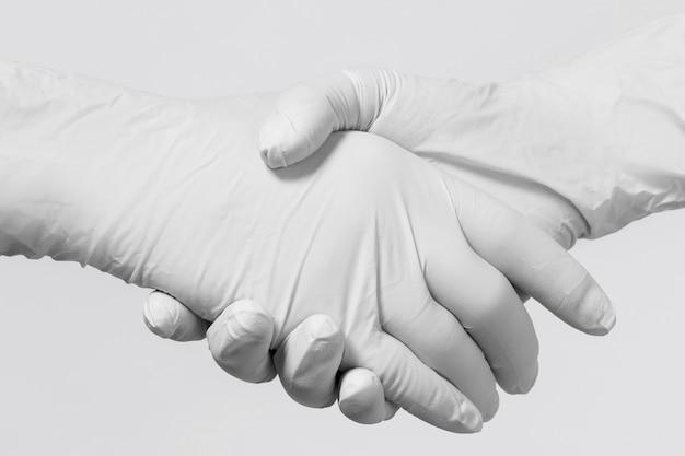 Händedruck für die medizinische zusammenarbeit. leute, die latexhandschuhe tragen, begrüßen sich.