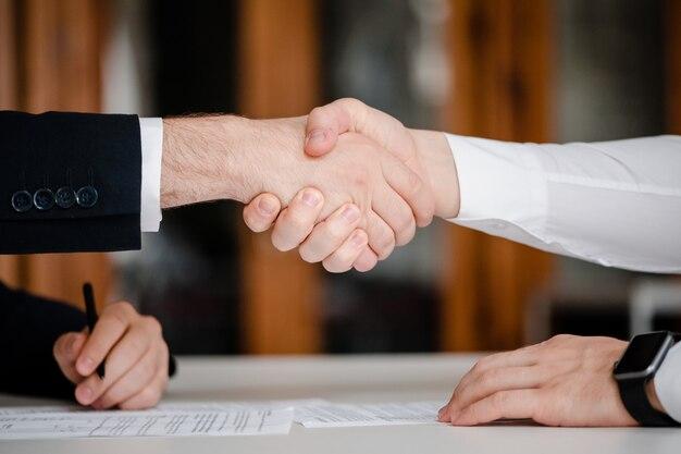 Händedruck von geschäftsleuten im büro mit einem vertrag zum unterzeichnen