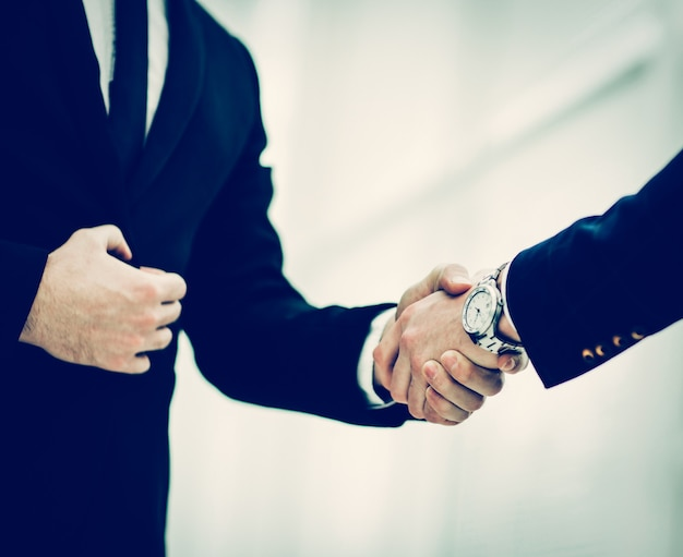 Händedruck von geschäftspartnern auf dem hintergrund des fensters in der moderne