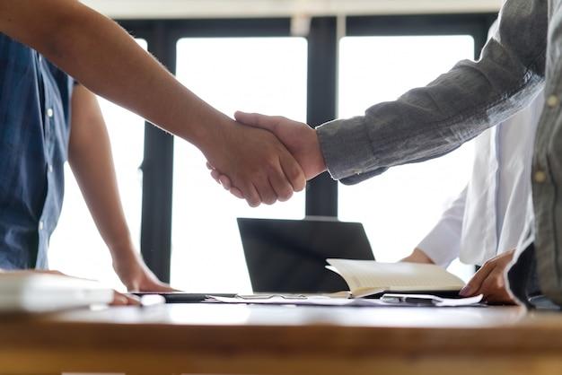 Händedruck zwischen zwei stehenden geschäftsleuten über der tabelle.