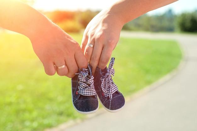 Händepaar, das babyschuhe für ungeborenes kind hält