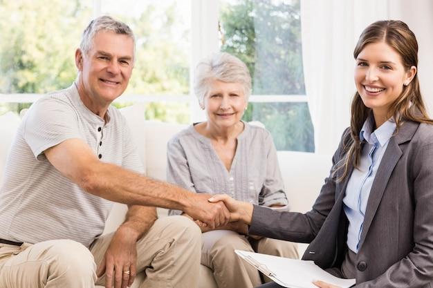 Händeschütteln der geschäftsfrau und des älteren mannes zu hause