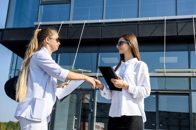 Händeschütteln der geschäftspartner vor dem bürogebäude. zwei schöne frauen in geschäftsanzügen lächeln sich an